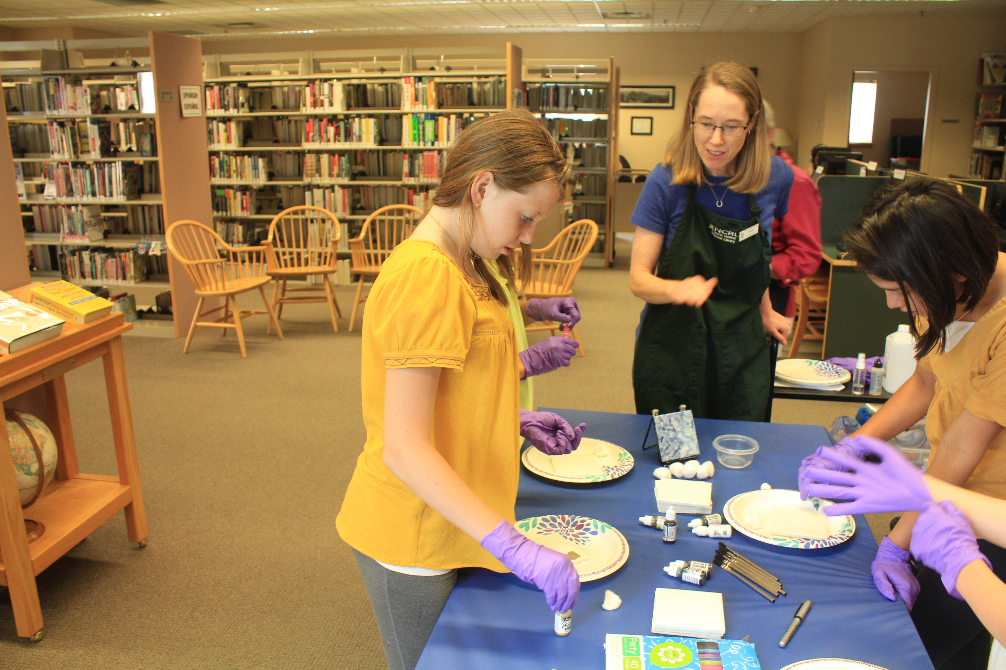 Librarian, Joanne Gembe, helps Adi Stimmel, age 13, and Celeste Villalobos, age 12, start the tile process.