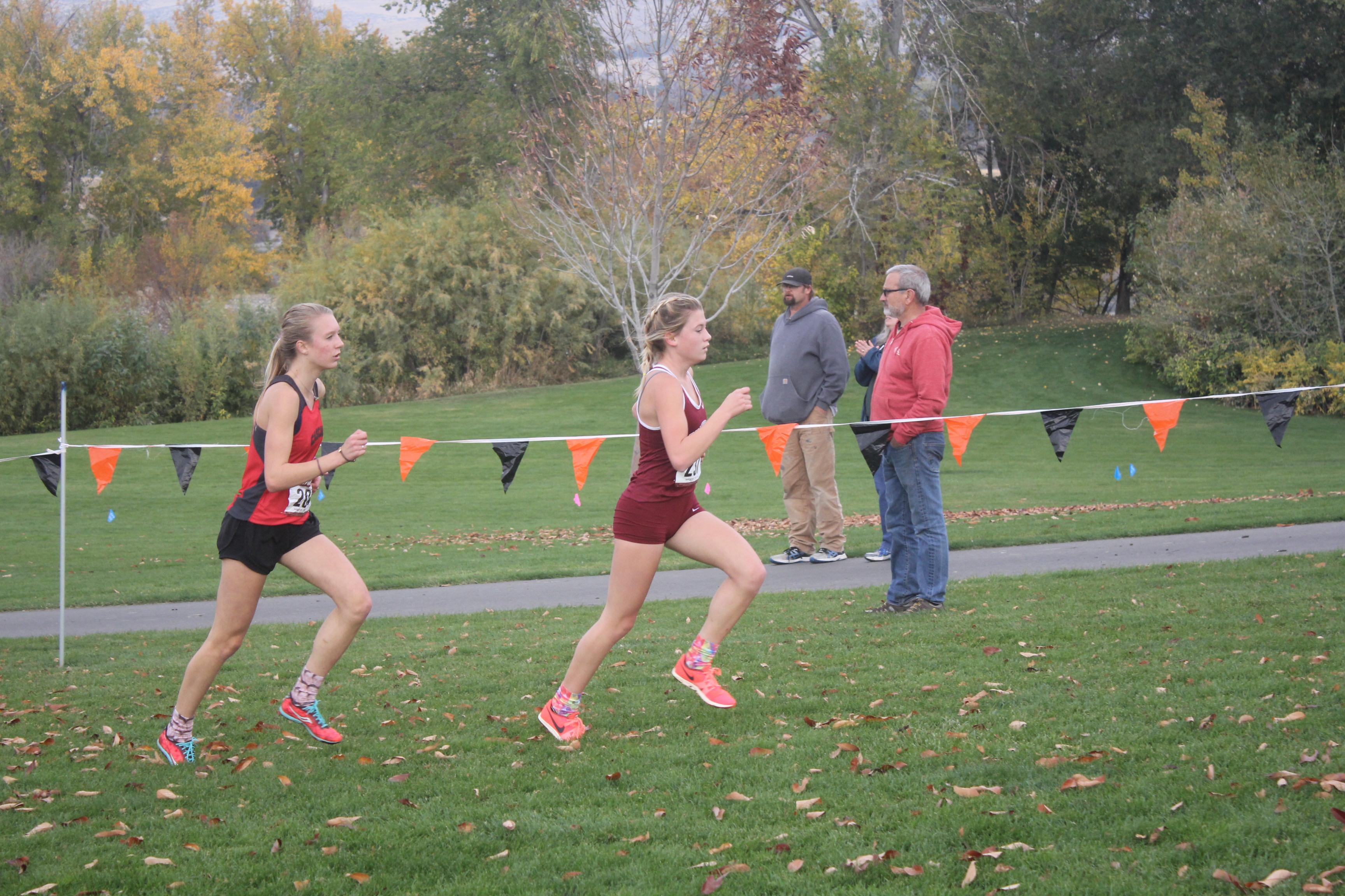 Zoe McDevitt pushes closer to passing the leader of the girls' varsity race.